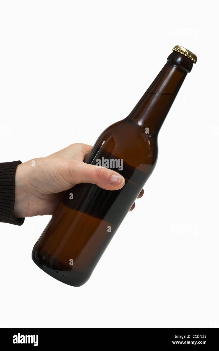 eine Bierflasche wird in der Hand gehalten   a beer bottle is hand-held - Stock Image