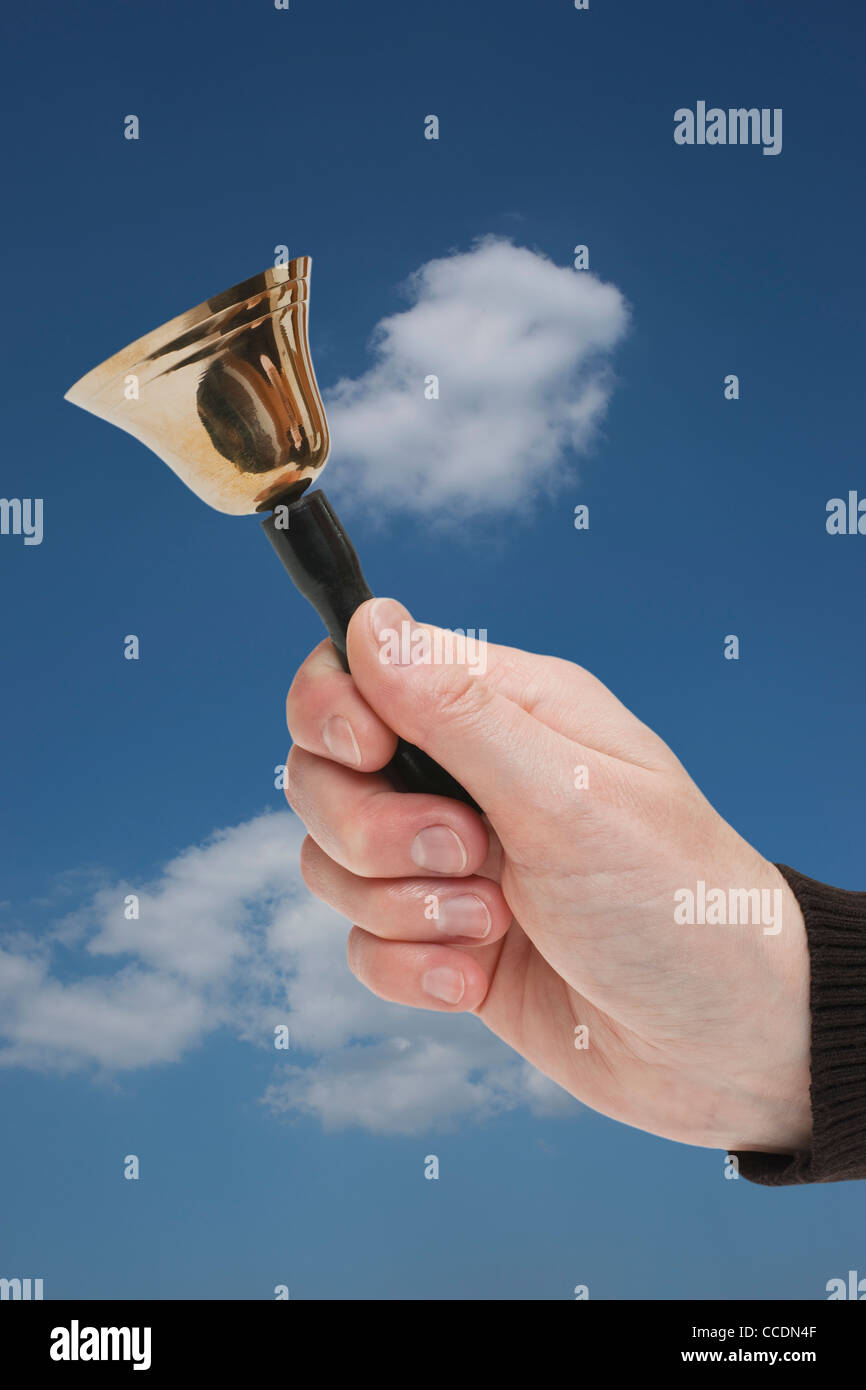 eine Handglocke wird in der Hand gehalten | a hand bell is hand-held - Stock Image