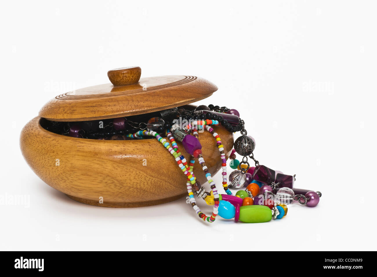 Detail photo of a round jewelery case, the top is open, jewelery hangs out. Stock Photo