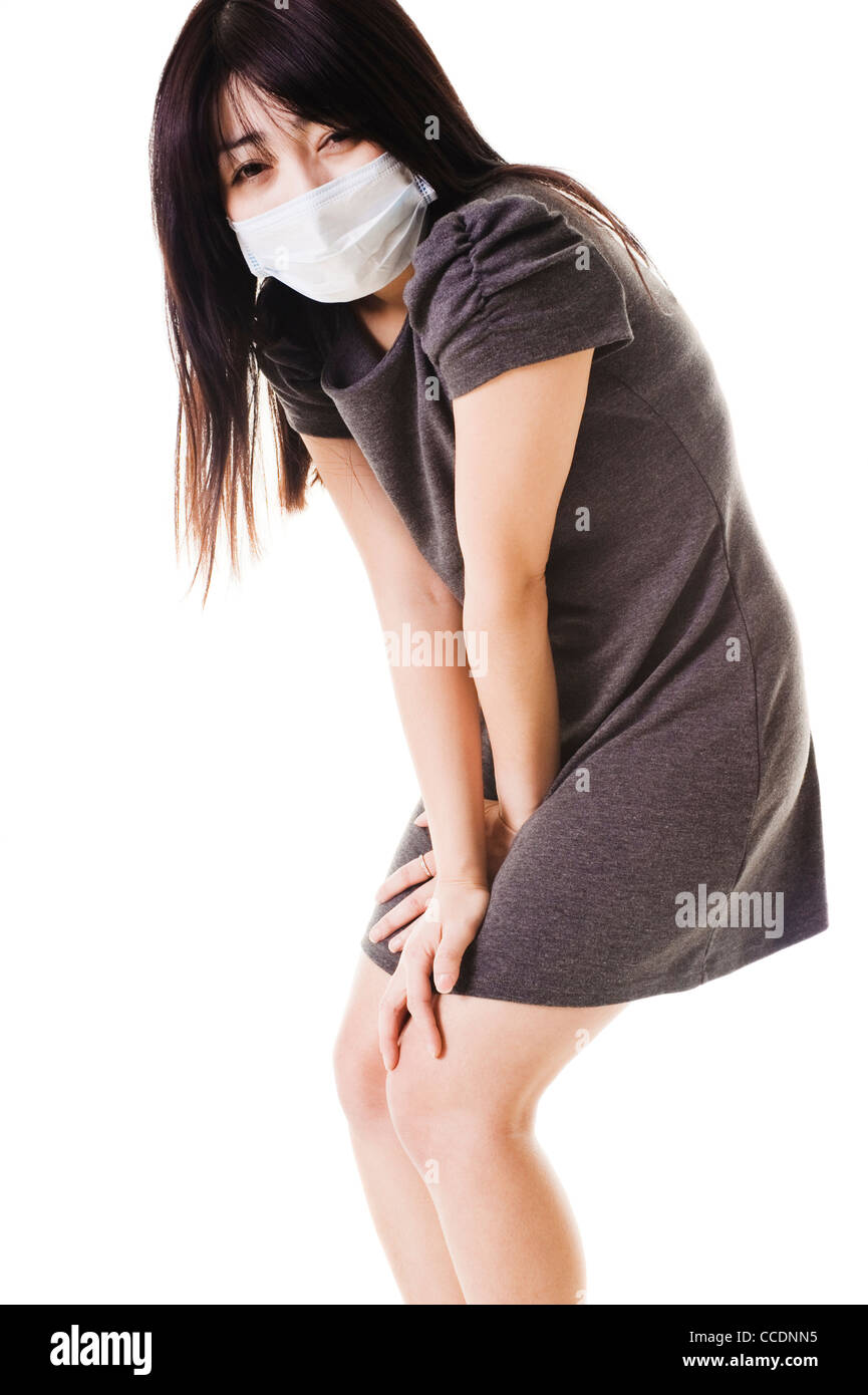 Sick Chinese woman wearing a face mask is bent over in pain. - Stock Image