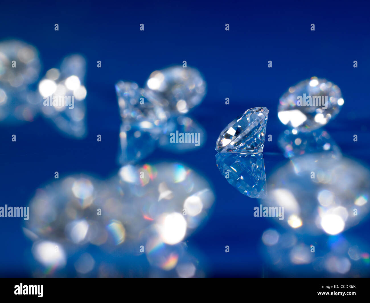 a group of diamonds on a blue reflective background - Stock Image