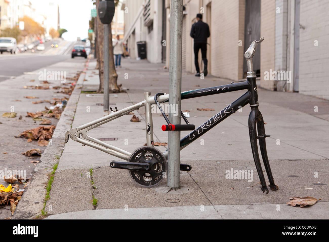 Vandalized bicycle on sidewalk (vandalized bike frame) - USA - Stock Image