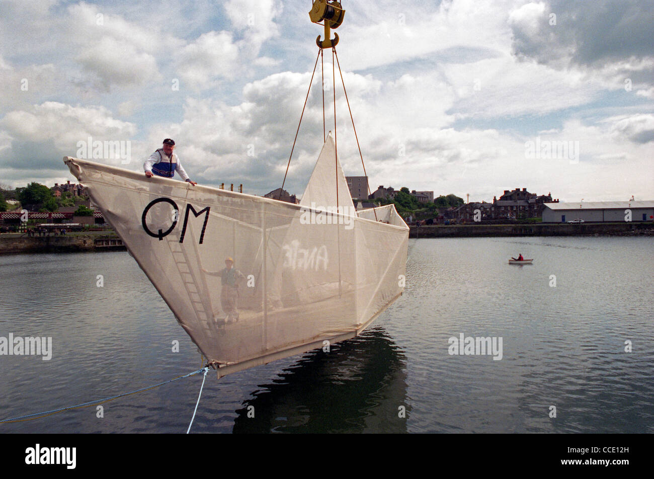 Sculptor George Wyllie's (on bow) Paper boat is craned into the water at the Consafe Shipyard in Burntisland, Fife Stock Photo