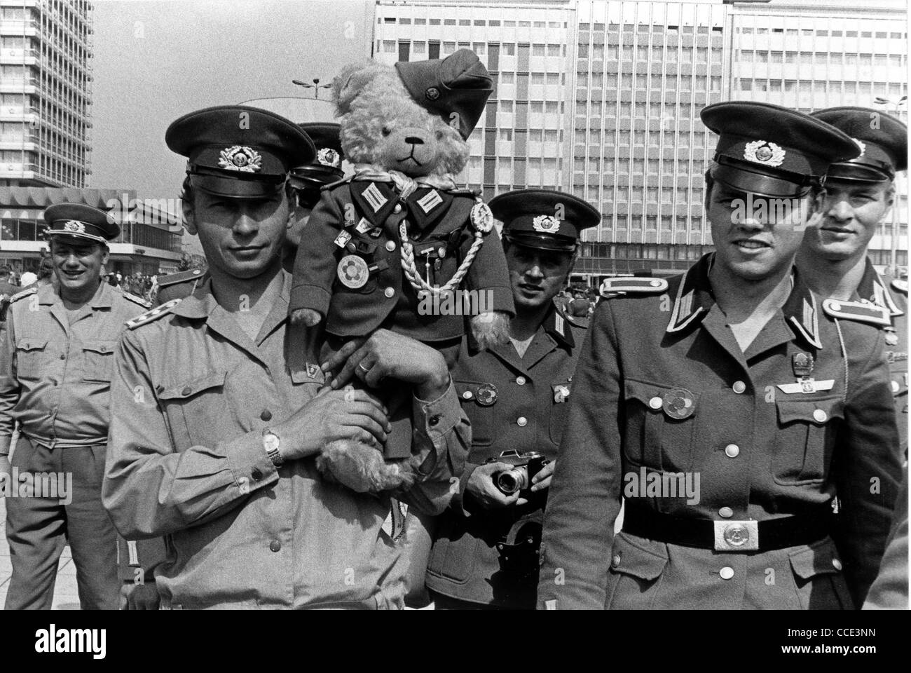 Soldiers of the National People's Army with a teddy bear in uniform in East Berlin. - Stock Image