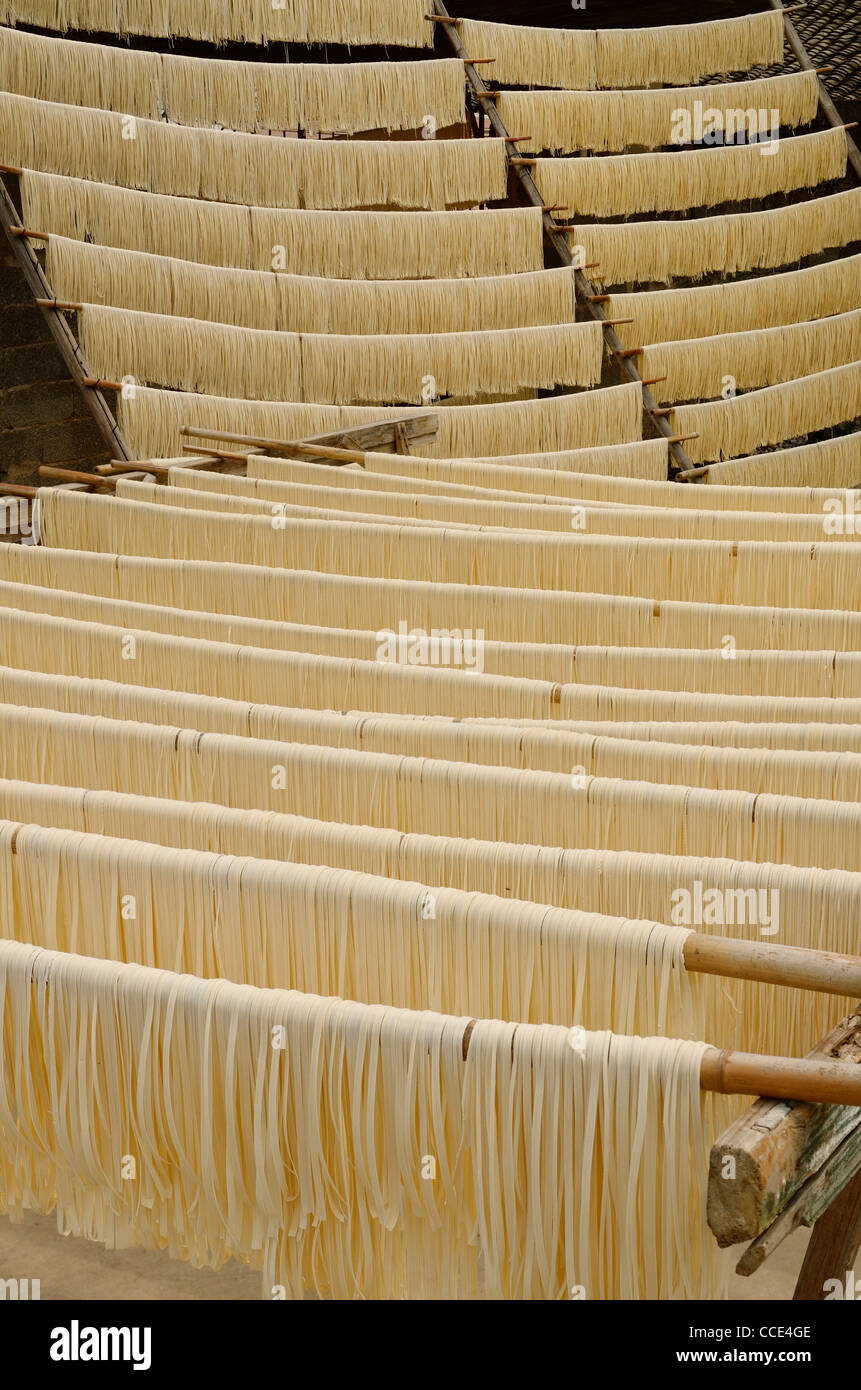Racks of raw noodles hanging outside to dry in Fuli near Yangshuo China - Stock Image