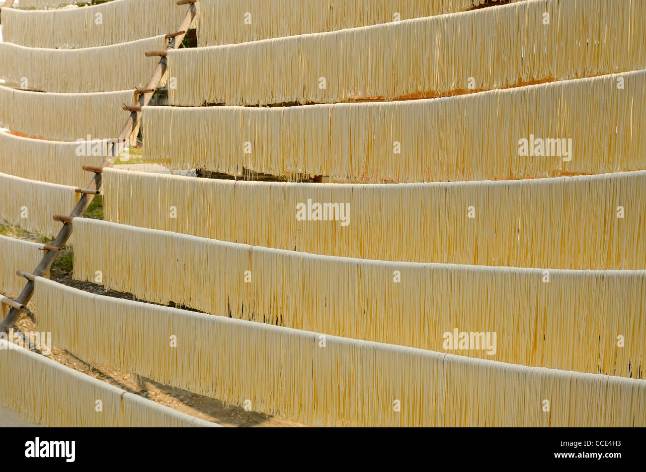 Noodles hanging out to dry on rods in Fuli near Yangshuo China - Stock Image