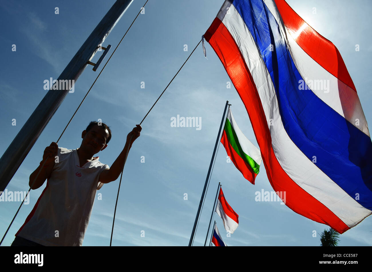A man raises flags at the riverside in Phnom Penh, Cambodia - Stock Image