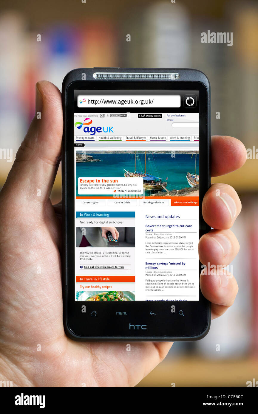 Looking at the Age UK charity website (an amalgamation of Age Concern and Help the Aged) viewed on an HTC smartphone - Stock Image