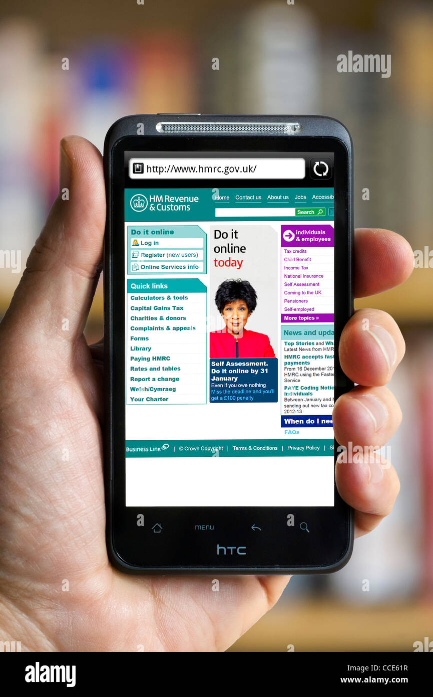 Looking at the HM Revenue and Customs website on an HTC smartphone - Stock Image