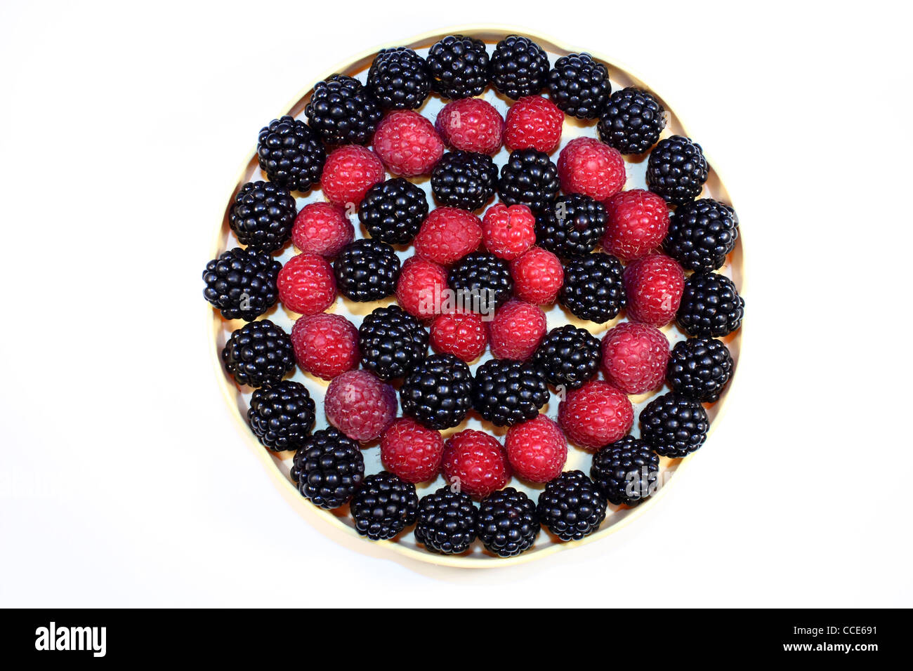 Fresh raspberries and blackberries in a little dish, ordered in a circle - Stock Image