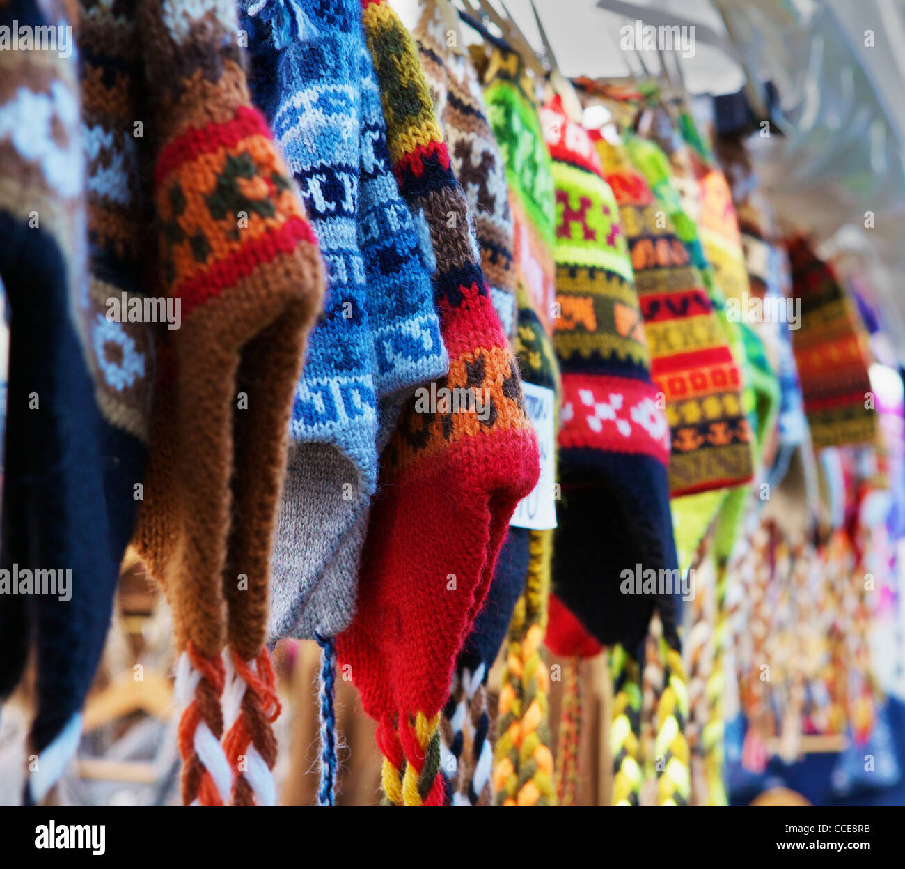 A row of colorful Alpaca wool knit hats in a row at a market - Stock Image