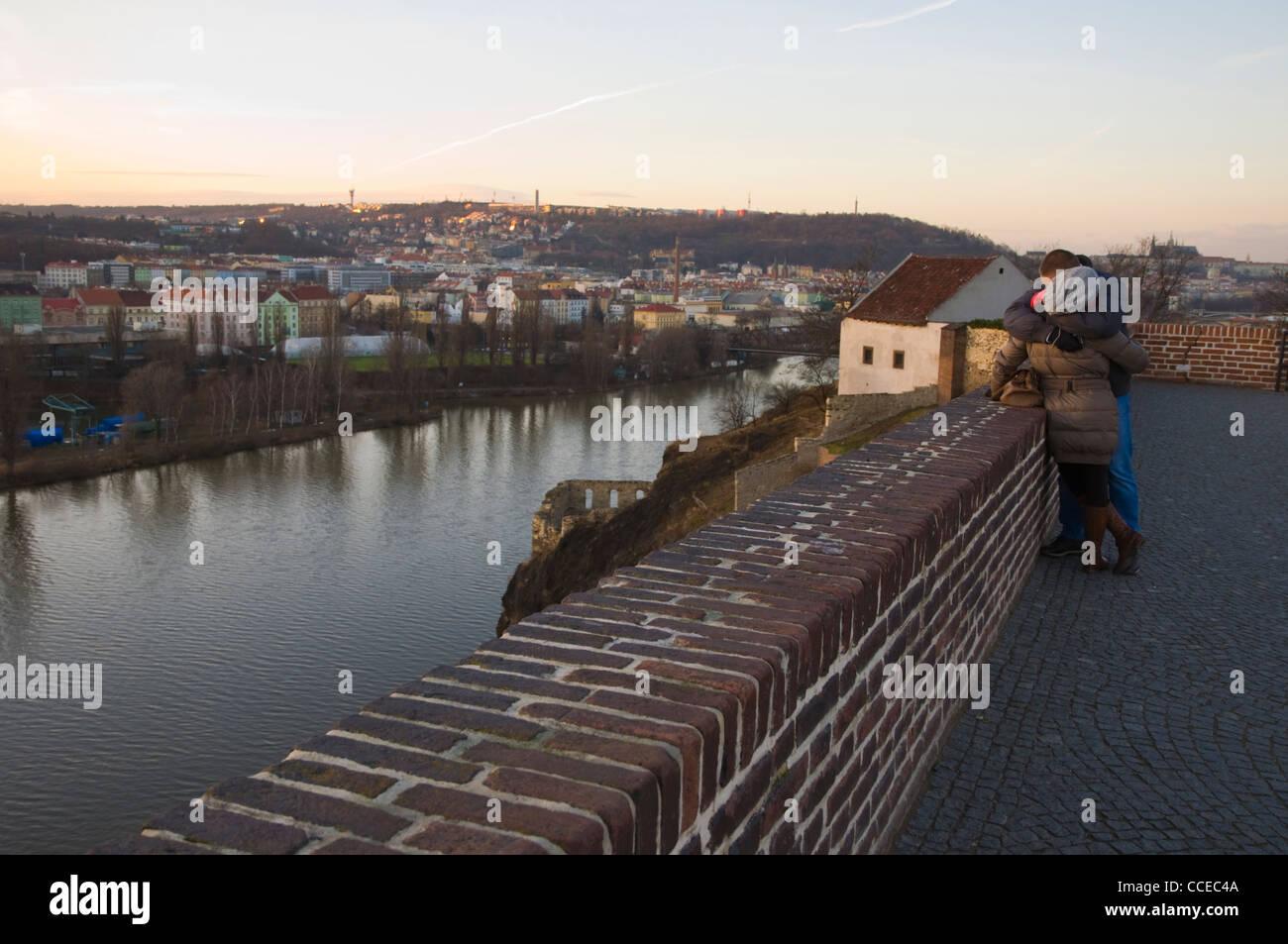 Couple at dusk on Vysehrad ramparts with Vltava riverside winter views Prague Czech Republic Europe - Stock Image