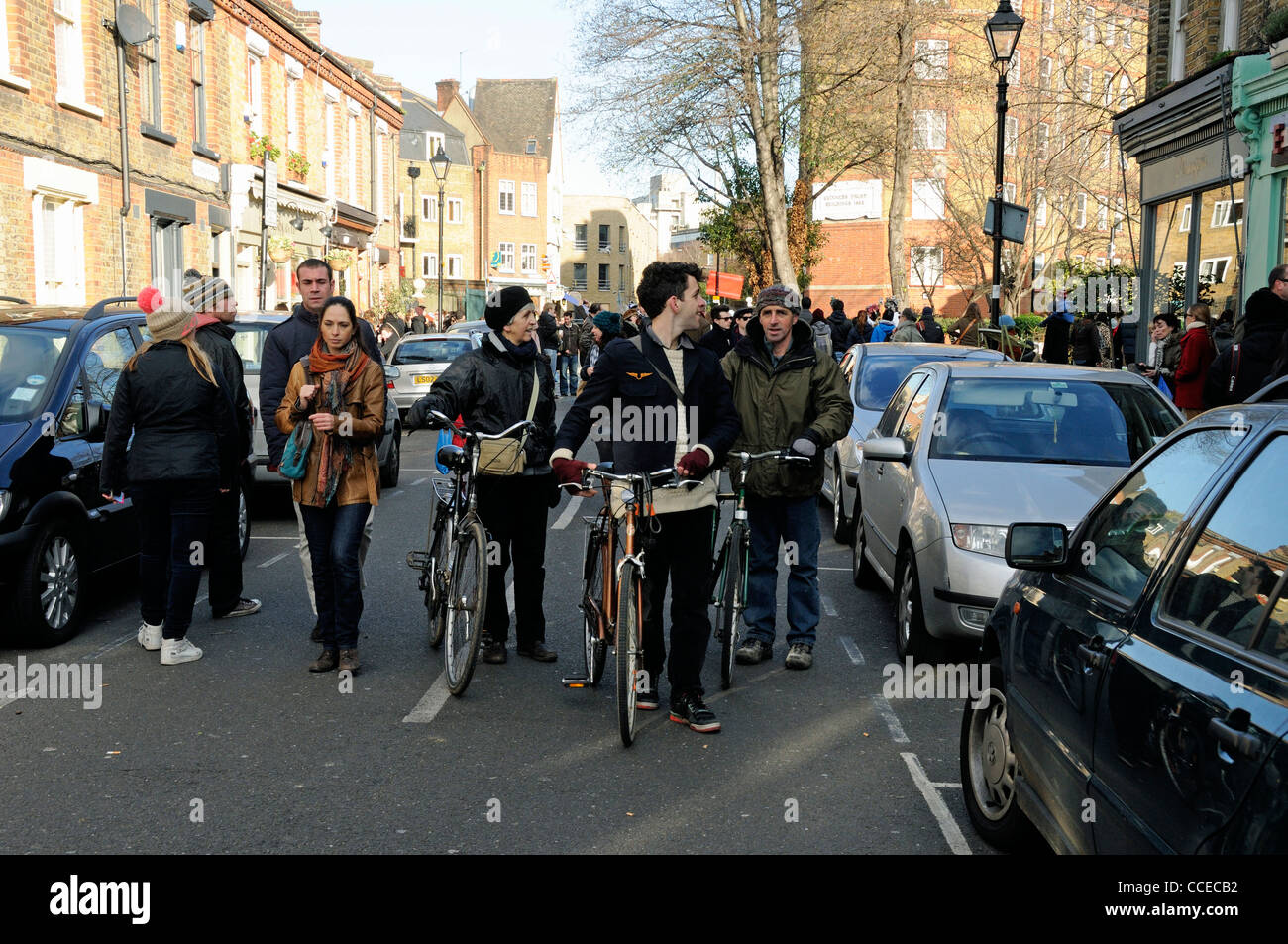 Cyclists pushing their bikes in Columbia Road Flower Market Tower Hamlets London England UK - Stock Image