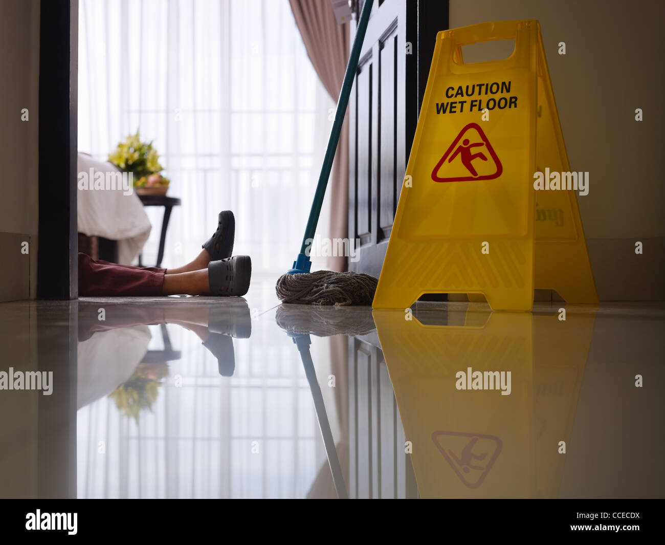 housemaid had accident at work while cleaning floor in hotel room. Side view, low angle - Stock Image