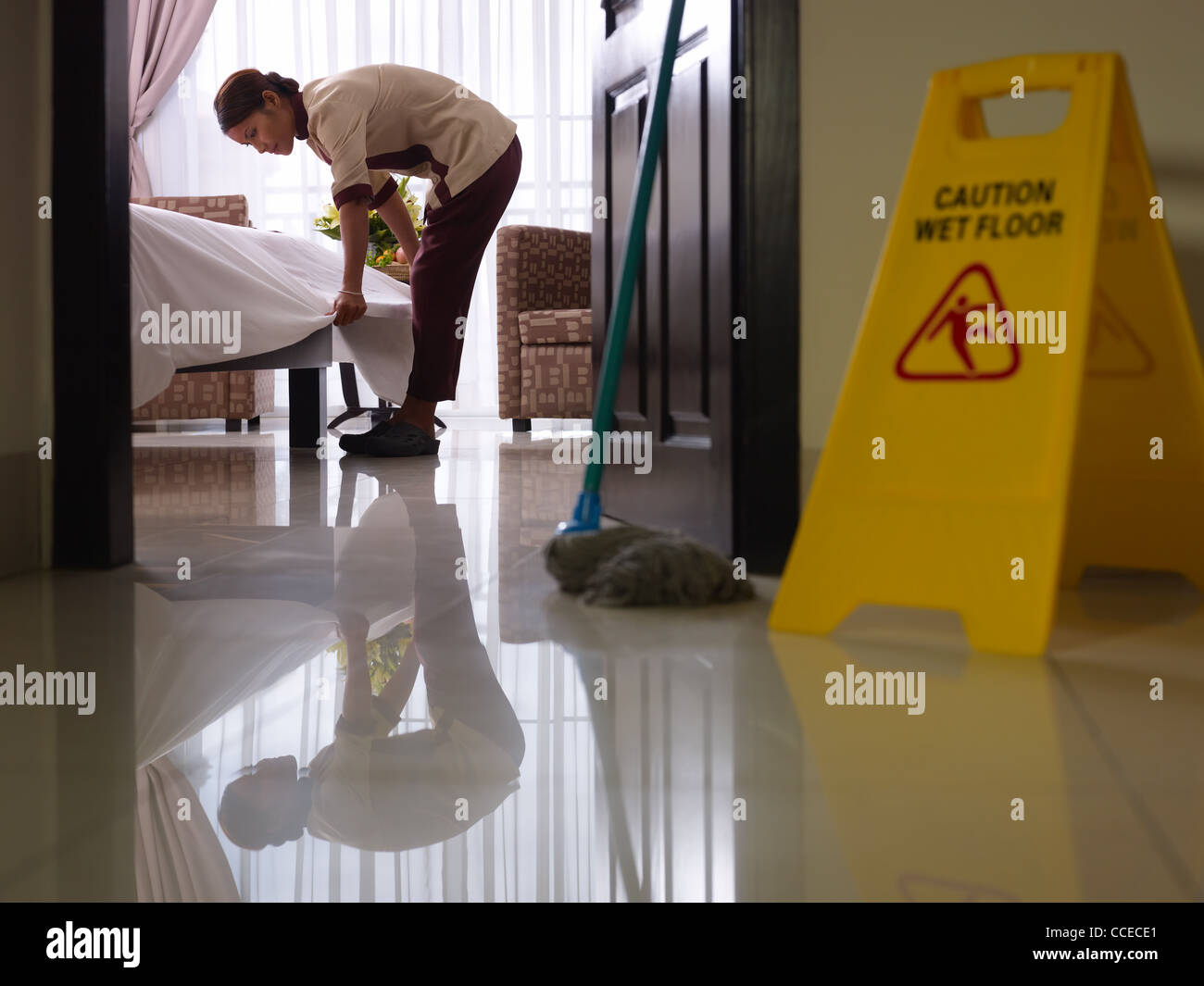 Asian maid tidying up bed and cleaning luxury hotel room - Stock Image