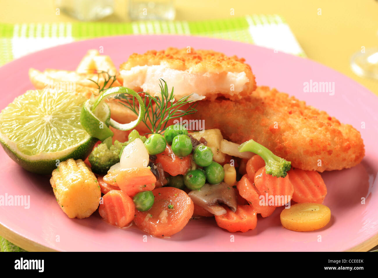 Fried fish served with French fries and mixed vegetables - Stock Image