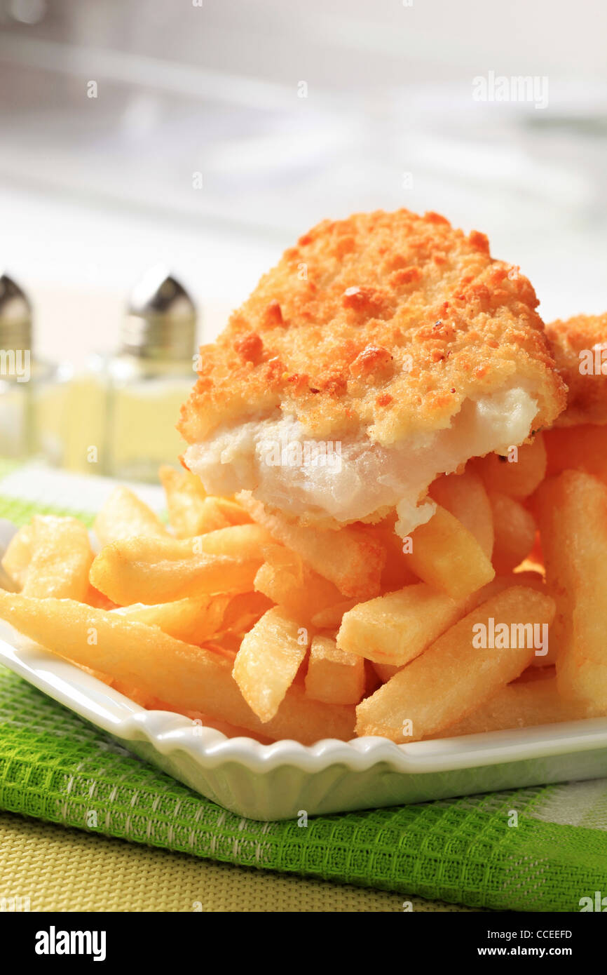 Fried fish fillet and heap of French fries - Stock Image
