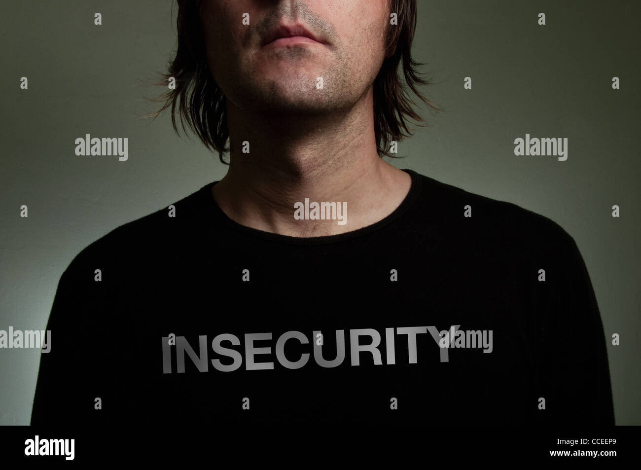 Man wearing a black shirt with 'Insecurity' title on his chest. Shiness, insecurity, solitude concept image. - Stock Image