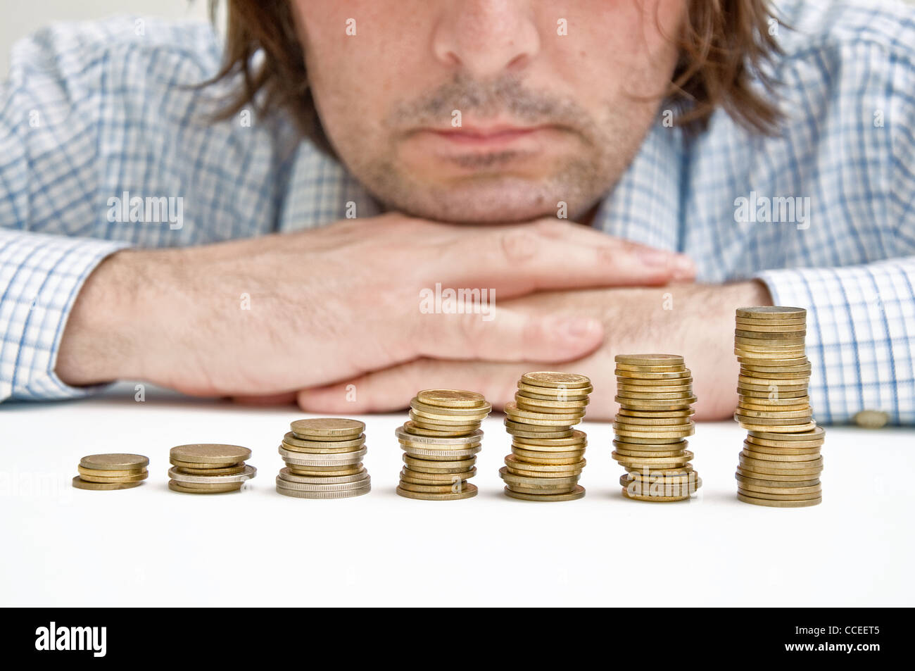 Businessman siting at the table and thinking about possible dollar investments. Stock Photo