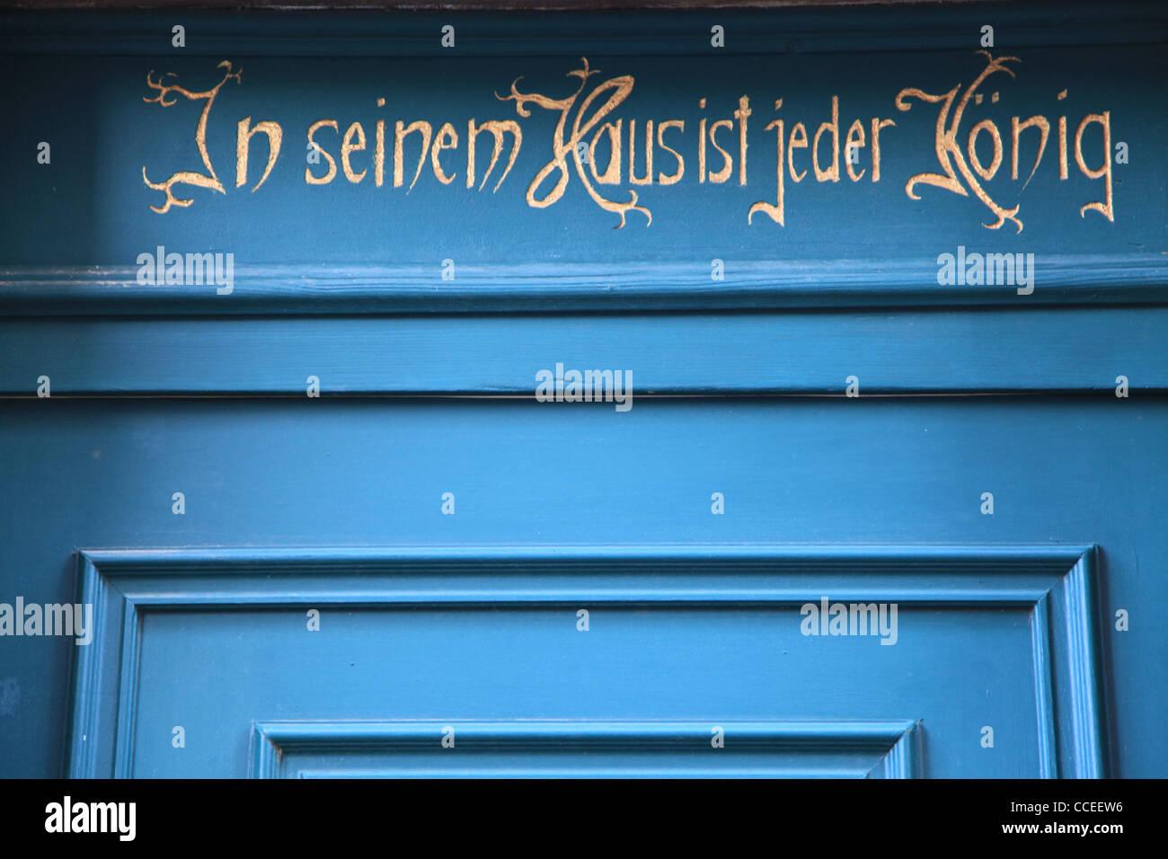 Haustür,door,historisch,historic,Deutschland,Germany,Kasettentür,blau,rot,schwarz,Rechteck,Inschrift,Sonnenschein,Idyll,idyll - Stock Image