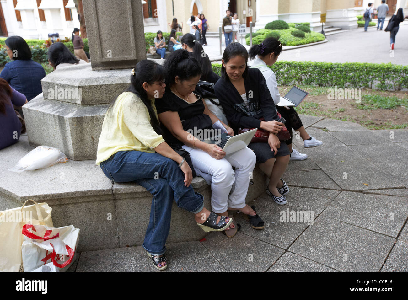 filipino and chinese domestic staff on their day off surf the net on wifi netbooks hong kong hksar china asia - Stock Image