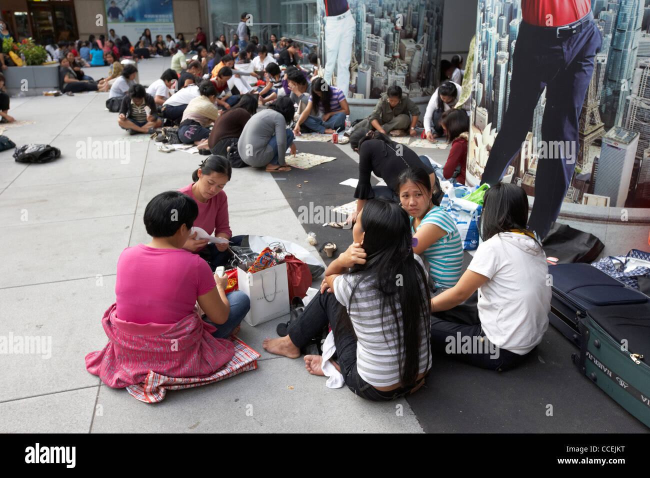 filipino and chinese domestic staff on their day off sitting in groups on the pavement outside hsbc building hong - Stock Image