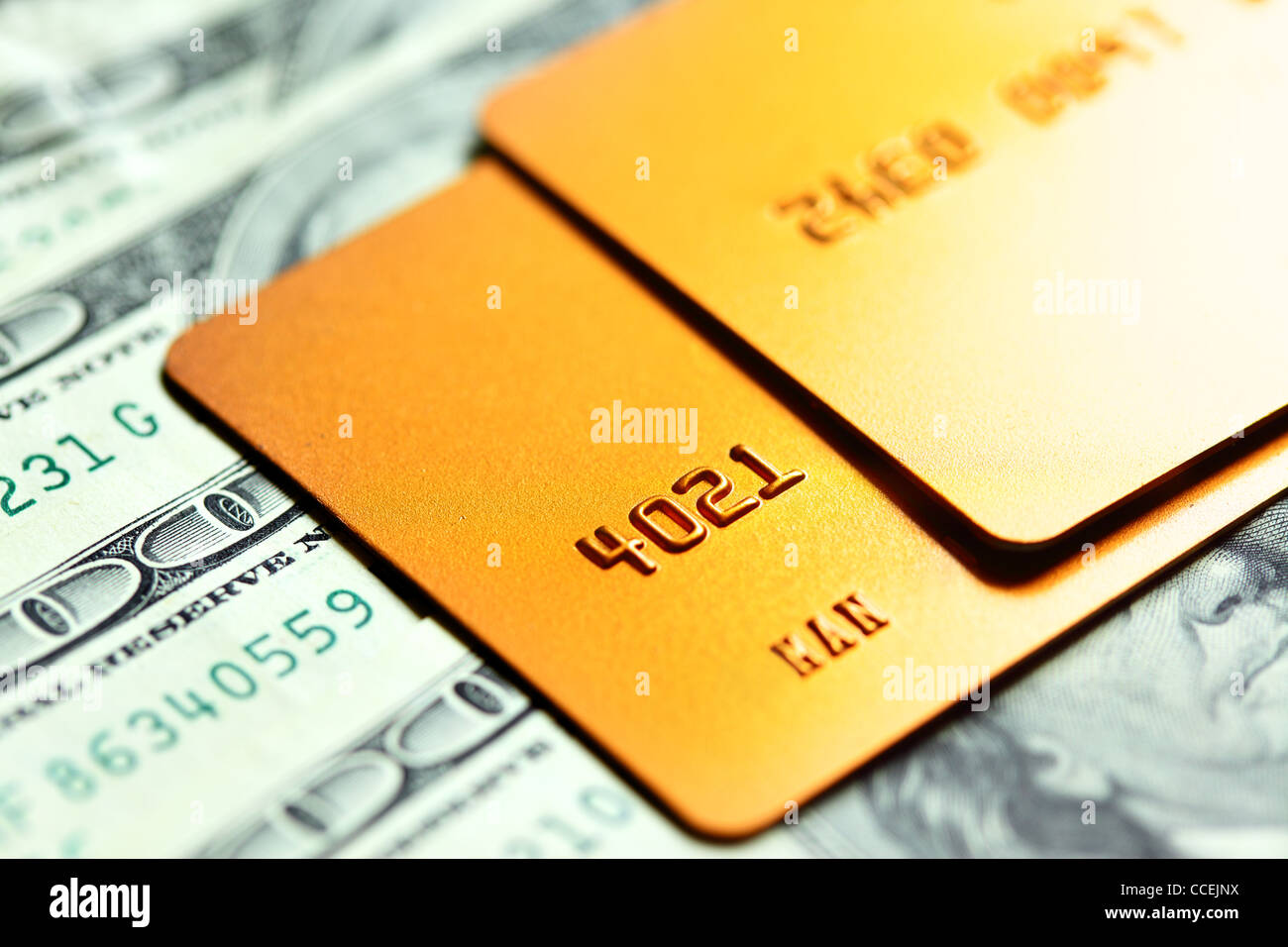 Gold credit cards on dollar notes. Shalow DOF! - Stock Image