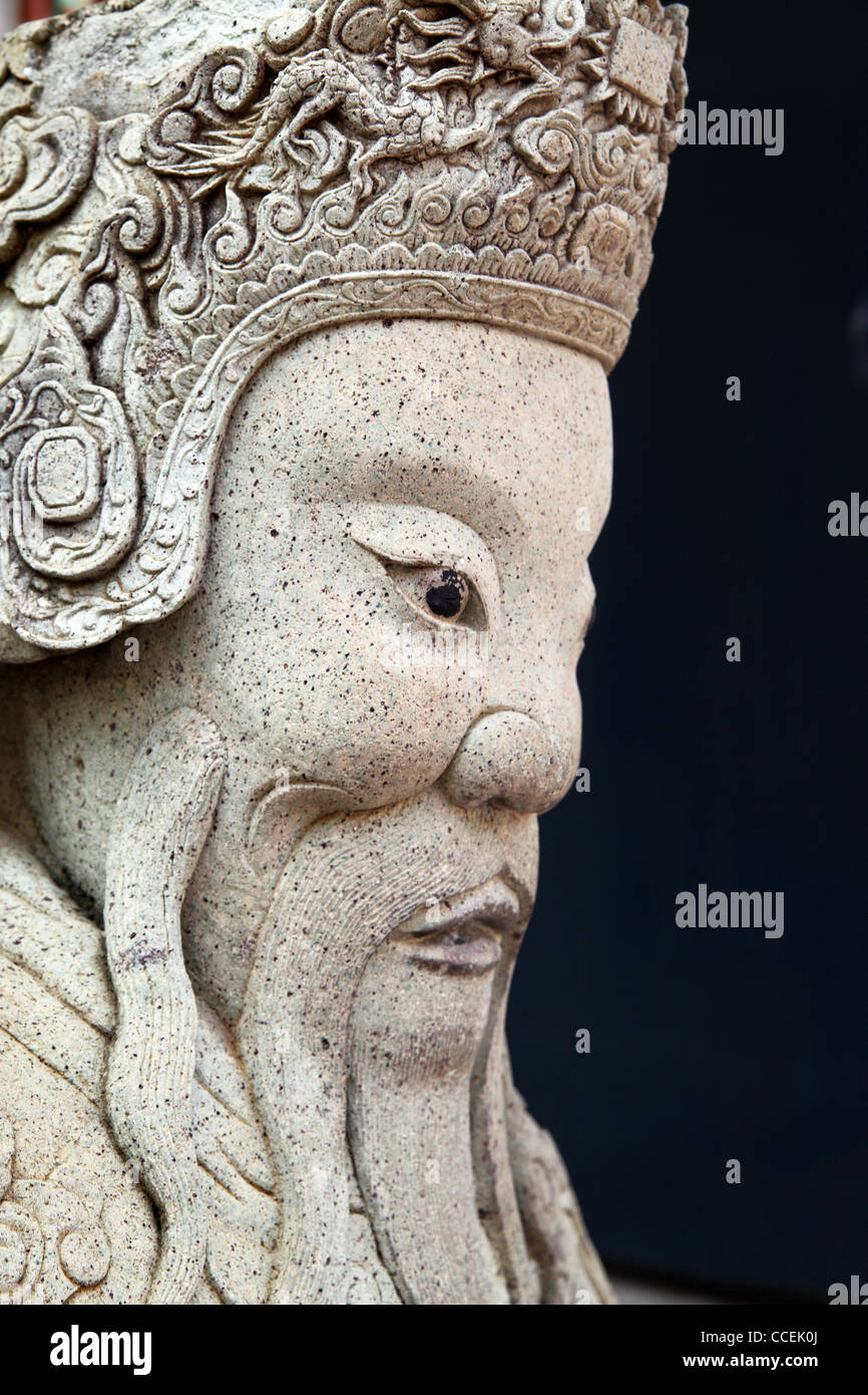 Ancient asian statue close-up over black gackground  - Stock Image