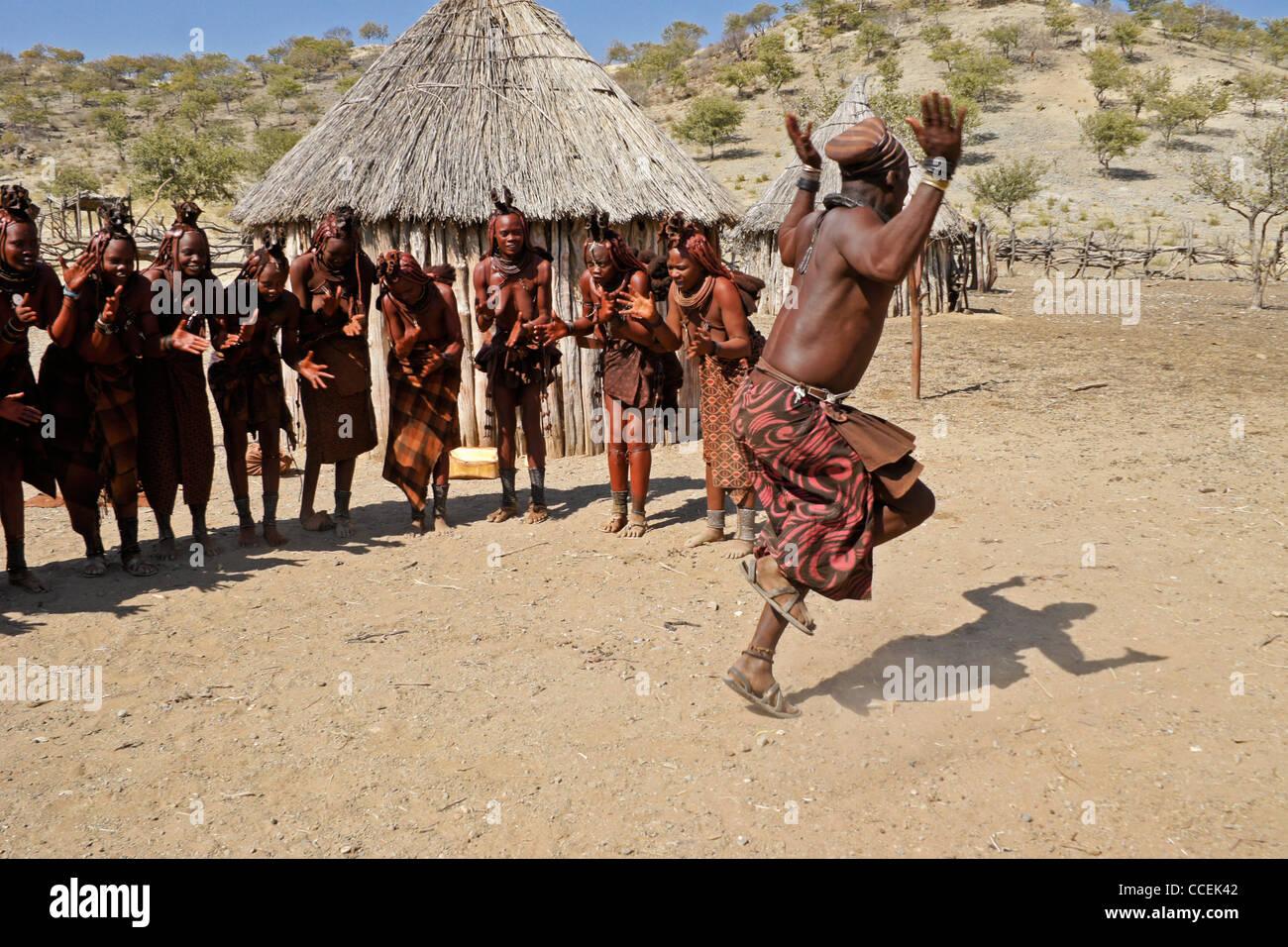Himba women singing and man dancing in village near Opuwo, Namibia - Stock Image