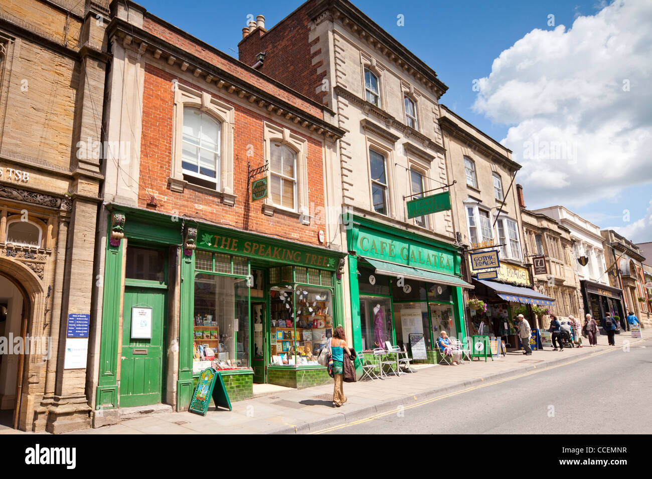 Shops and cafes and people shopping in High Street, Glastonbury, Somerset, England. - Stock Image