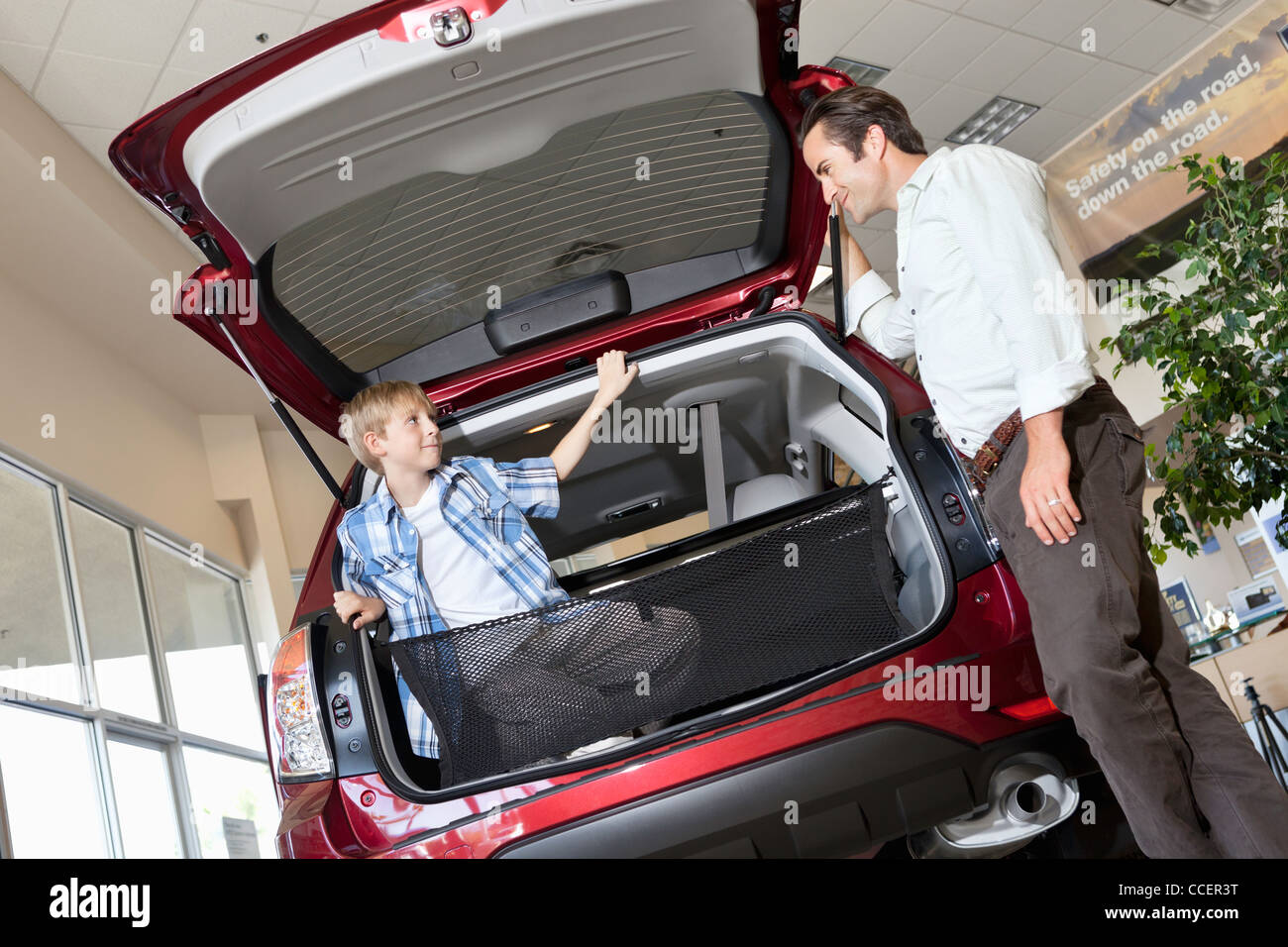 Father looking at son sitting in car trunk in showroom - Stock Image