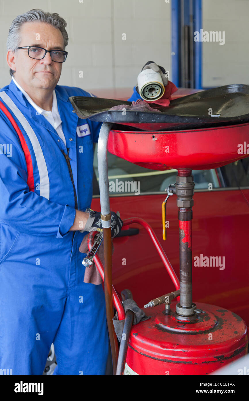 Portrait of senior mechanic standing besides car spray paint equipment - Stock Image