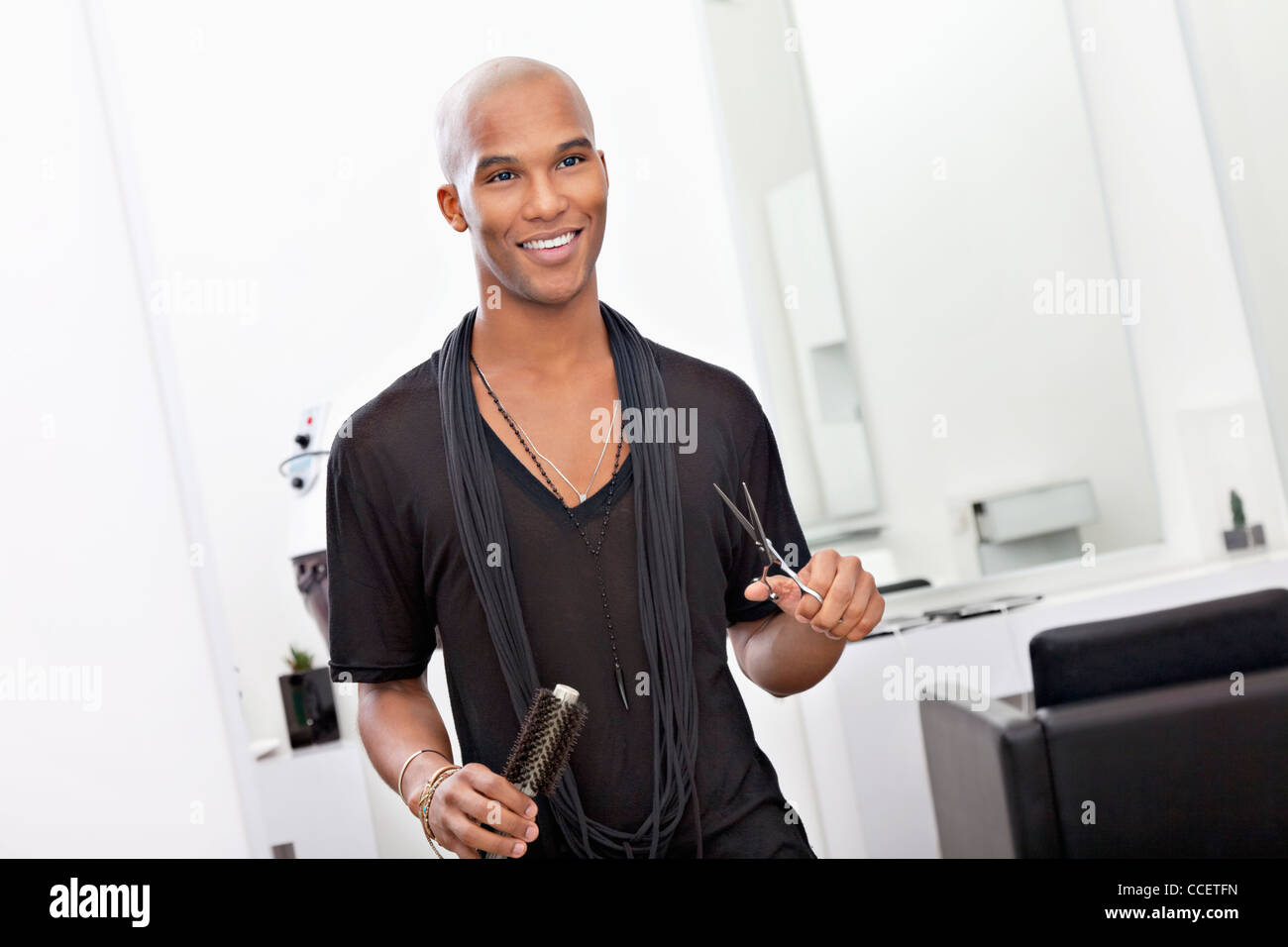 Smiling male hairdresser holding scissor and hairbrush - Stock Image