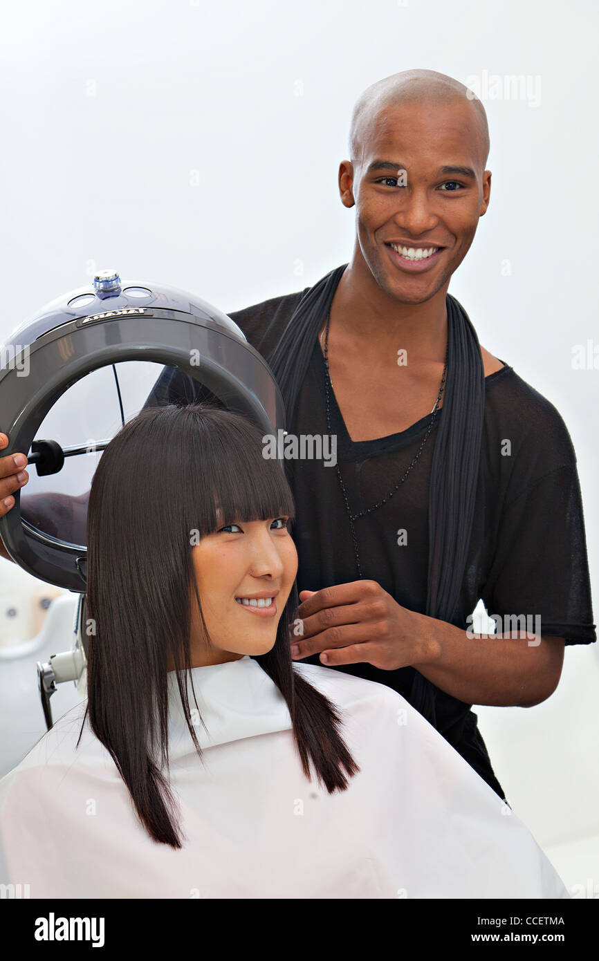 Asian woman getting herself groomed at hair salon - Stock Image