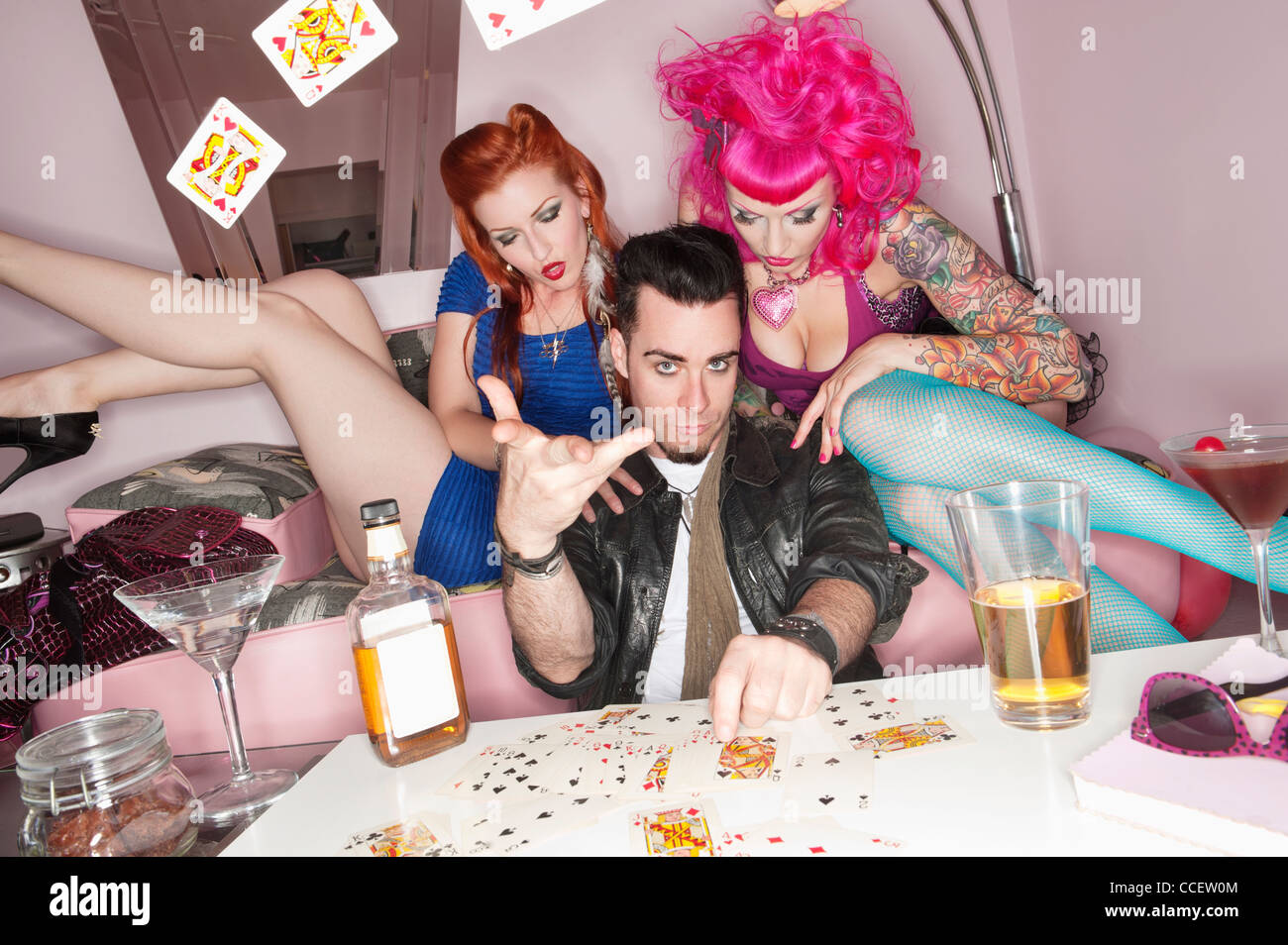 Man tossing playing cards in air with women sitting besides him Stock Photo