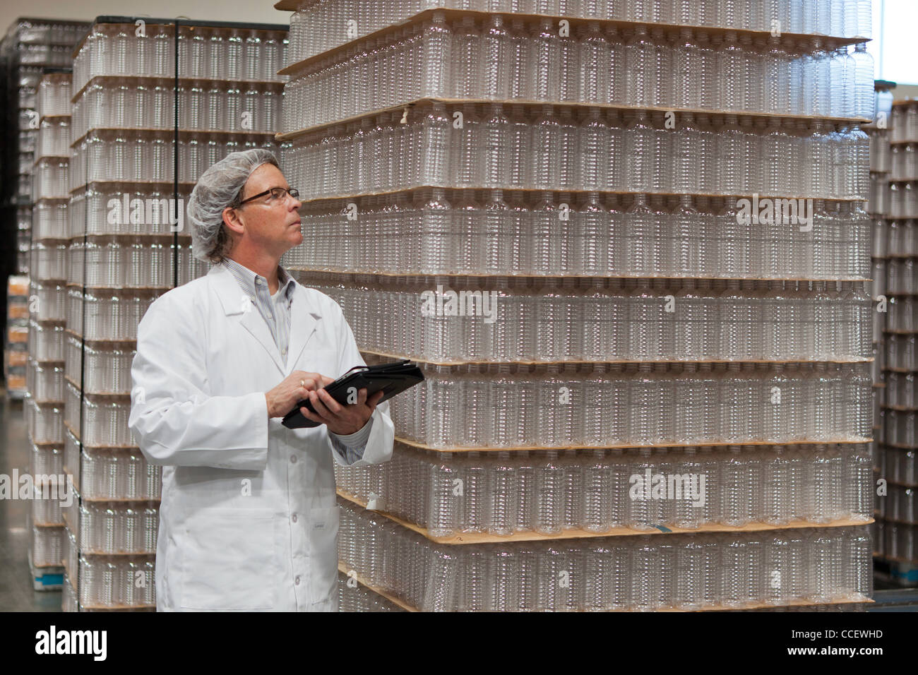 Man inspecting bottled water in distribution warehouse - Stock Image