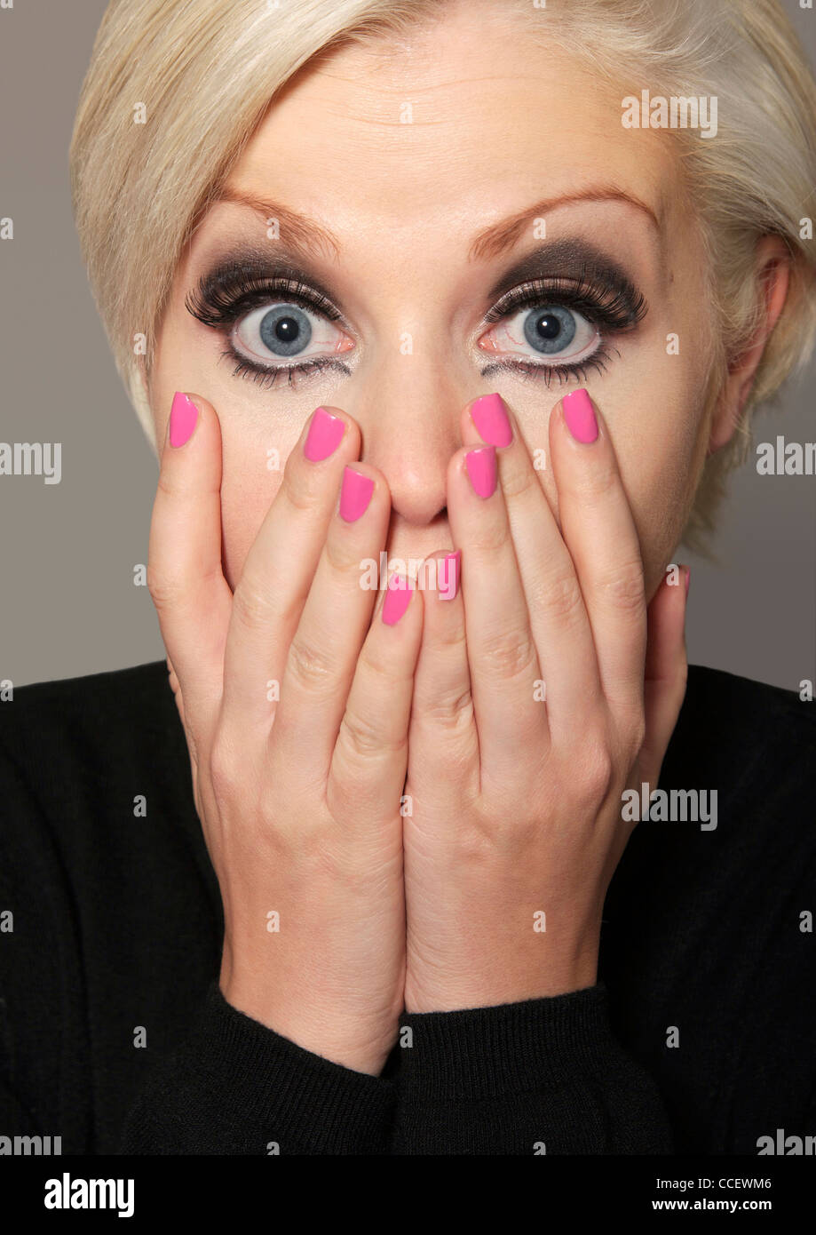 Shocked blonde-haired woman with hands on her face - Stock Image