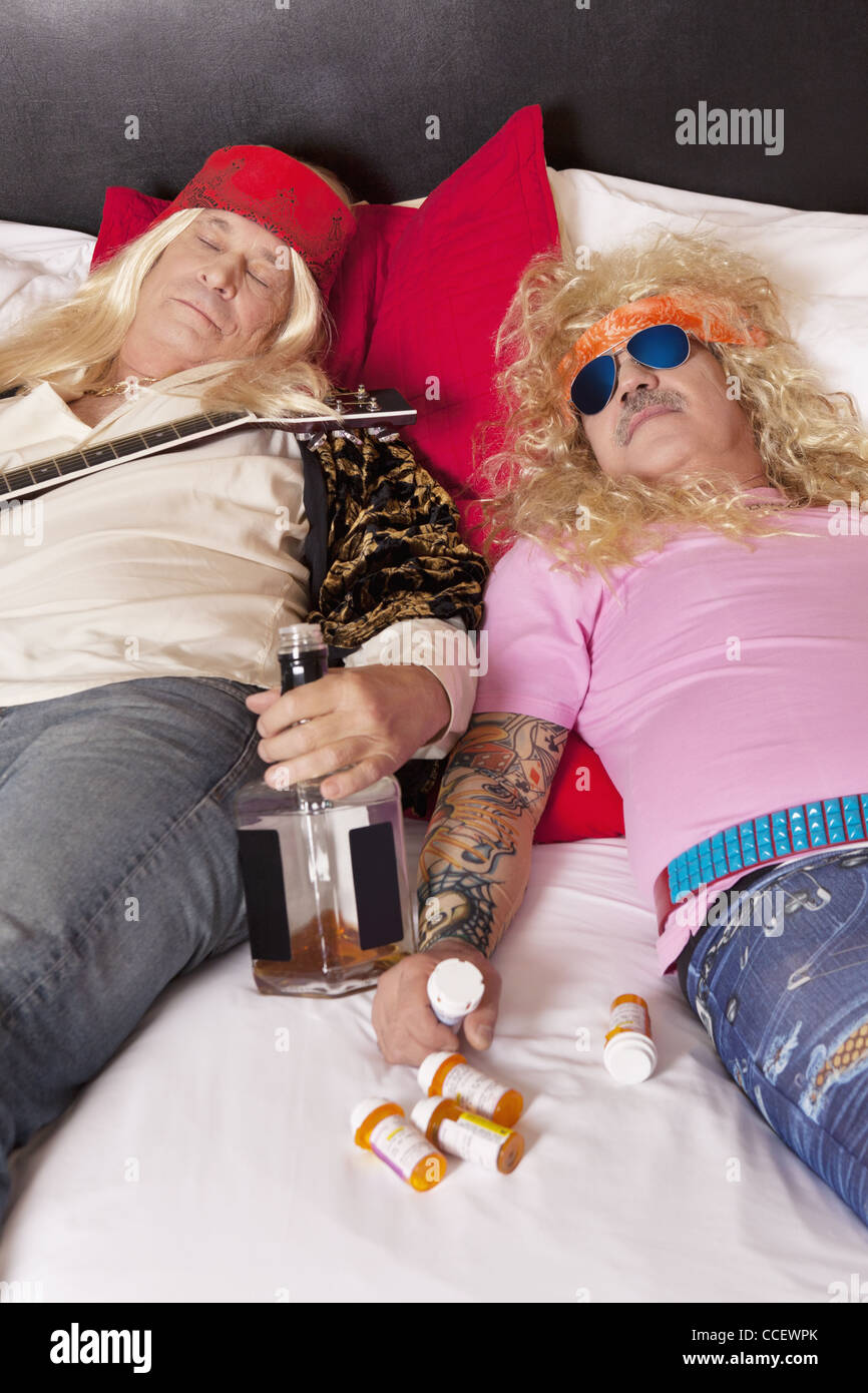 Two drunk male friends reclining on bed - Stock Image