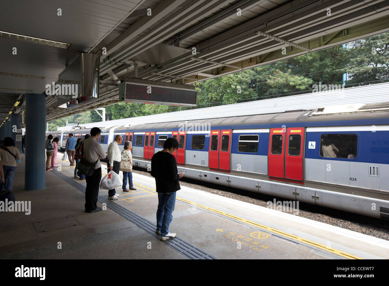 passengers waiting on the platform for train on mtr overground line former kcr kowloon canton railway kowloon tong - Stock Image