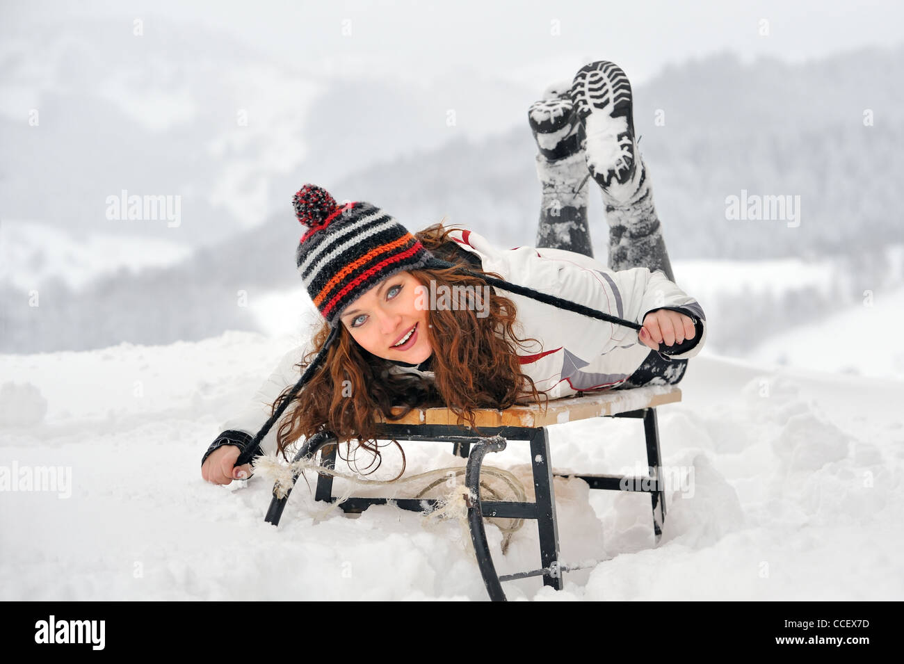 Young Beautiful Woman on sledge in winter time - Stock Image