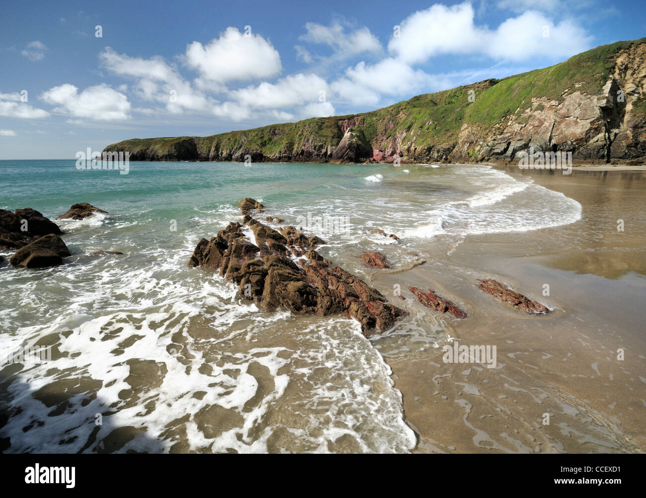 Caerfai Beach near the tiny city of St Davids on a sunny day with gentle surf lapping the shore - Stock Image