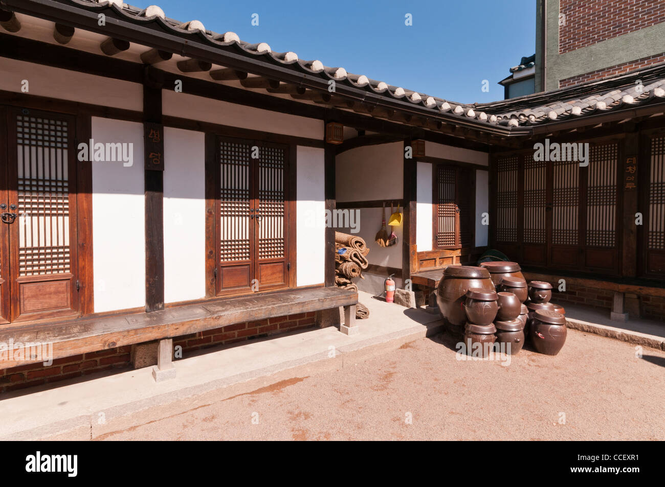 Hanok (Korean traditional house with timber frames and clay tiles) and its courtyard.  Clay pots are on display. Stock Photo