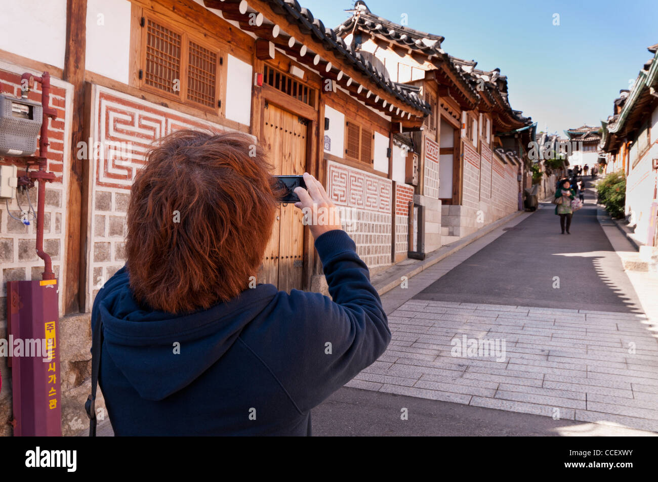 a tourist taking a photograph of traditional timber frame houses with his mobile phone in Bukchon Hanok Village, Stock Photo