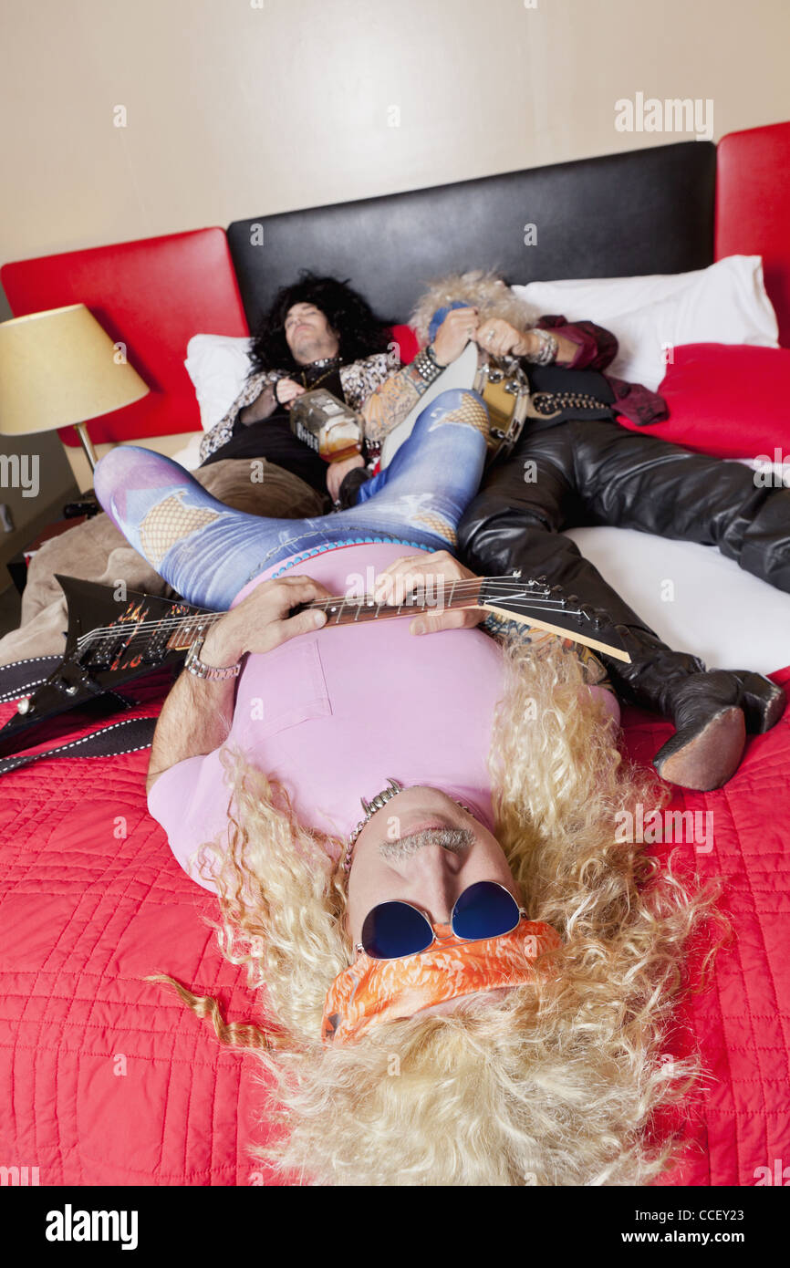 Three exhaust friends lying down on bed - Stock Image