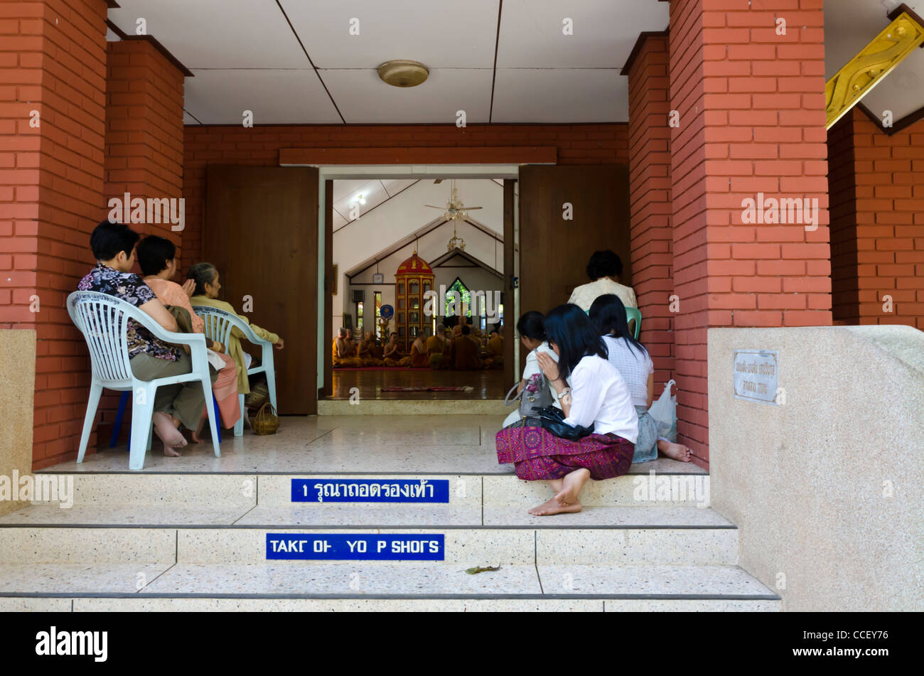Relatives watch Buddhist monk initiation ceremony from porch of building at Wat U Mong temple in Chiang Mai Thailand - Stock Image