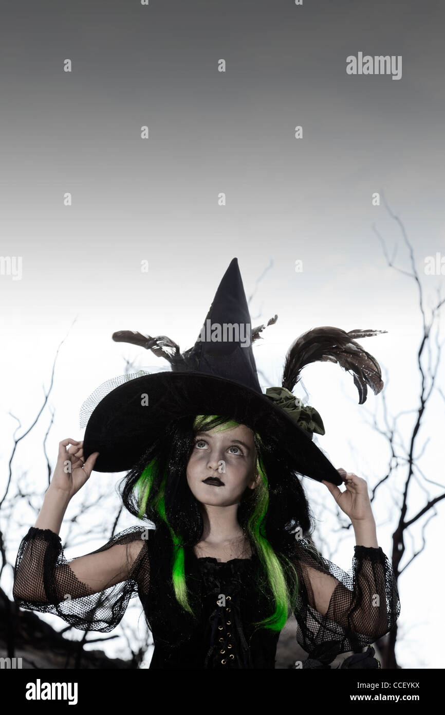 Girl costumed as witch looking up holding her hat - Stock Image