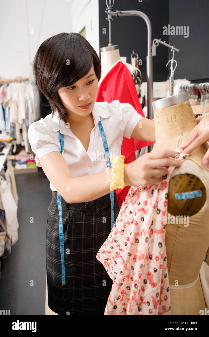 Female fashion designer pinning costume on mannequin - Stock Image