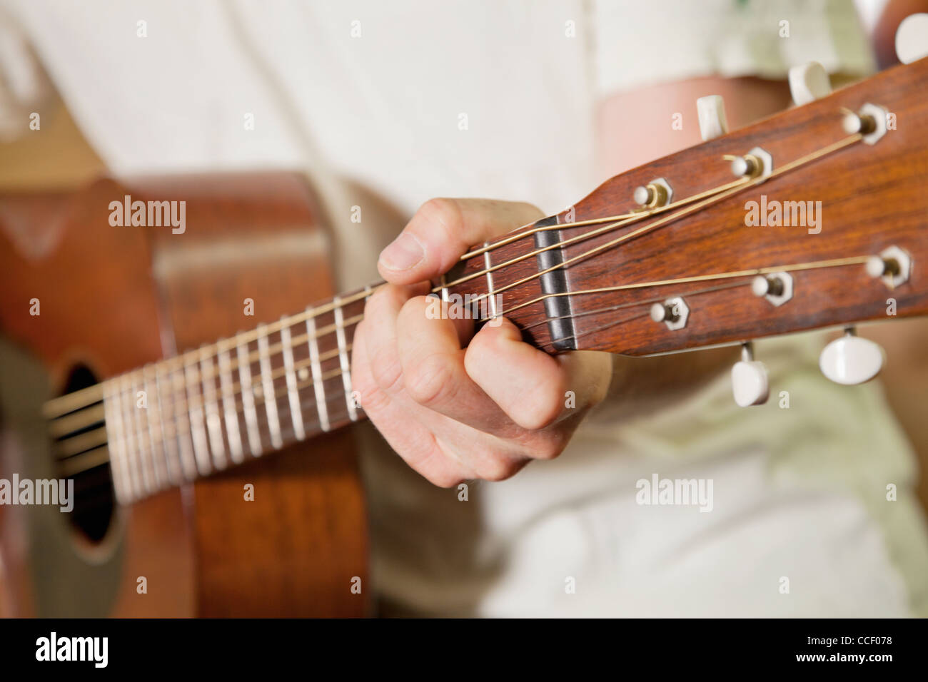 Close-up view of man's hand playing guitar - Stock Image
