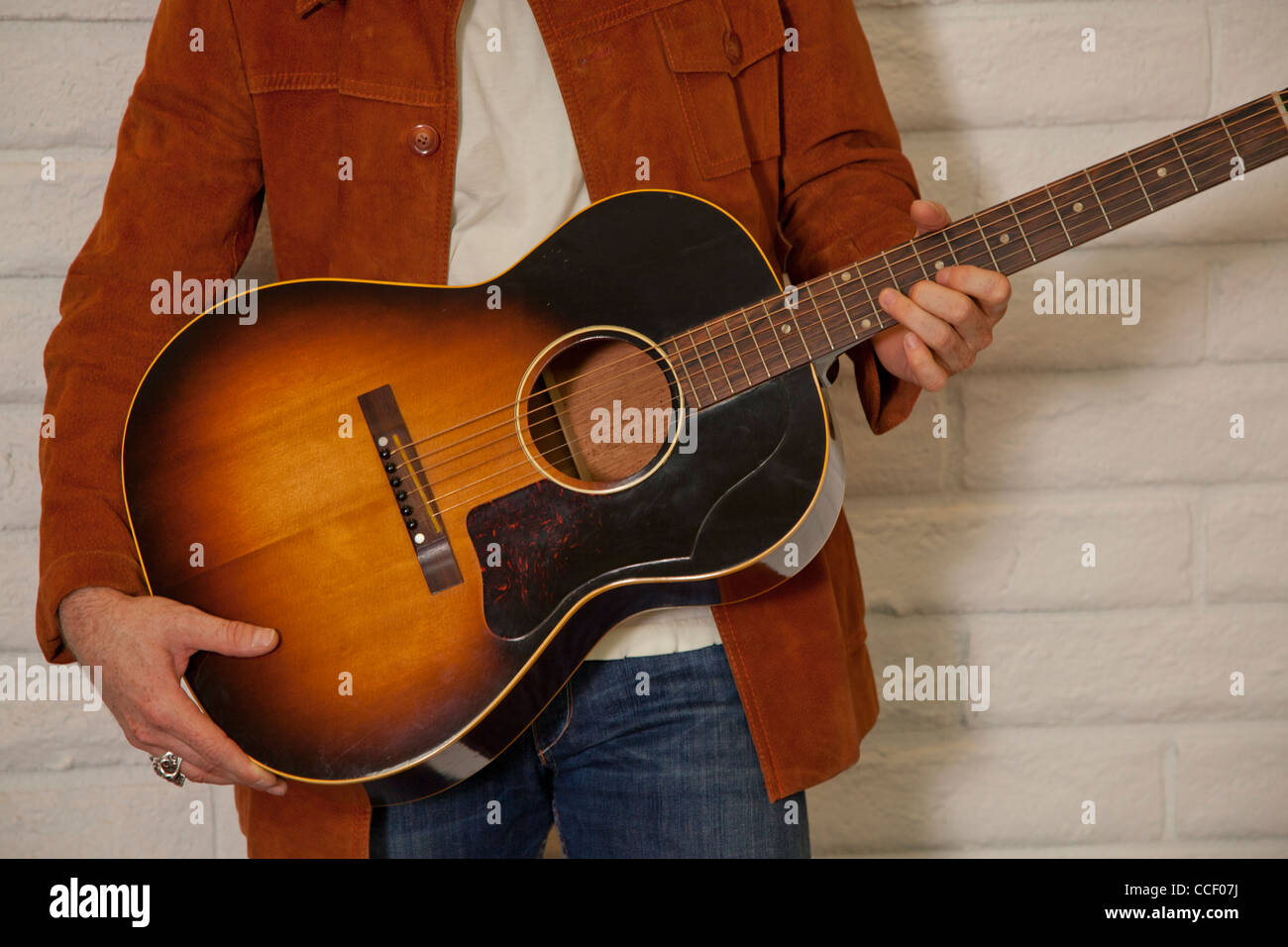 Close-up of mid adult man's torso holding guitar - Stock Image
