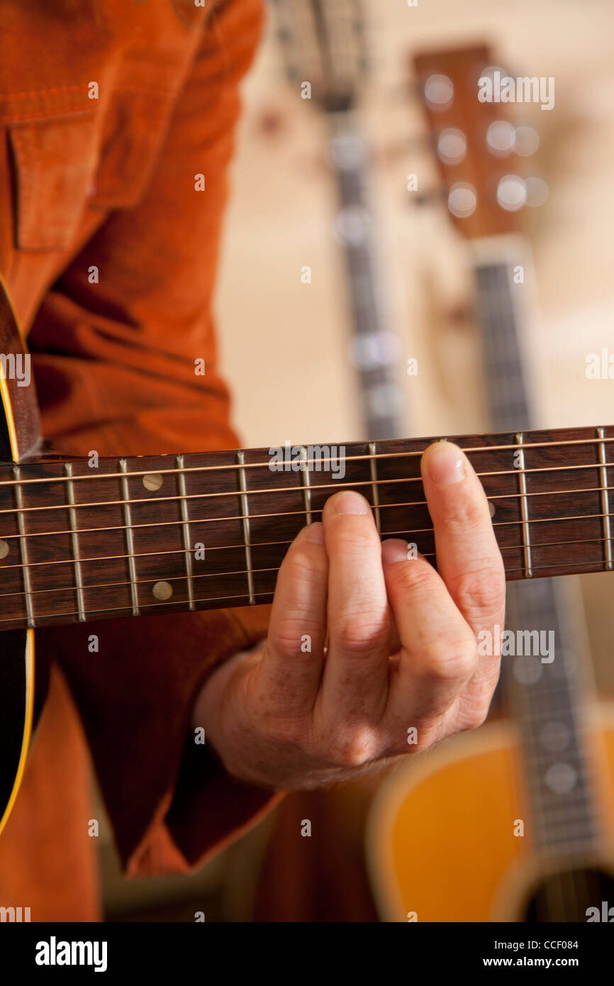 Close-up of mid adult man's fingers while playing guitar - Stock Image